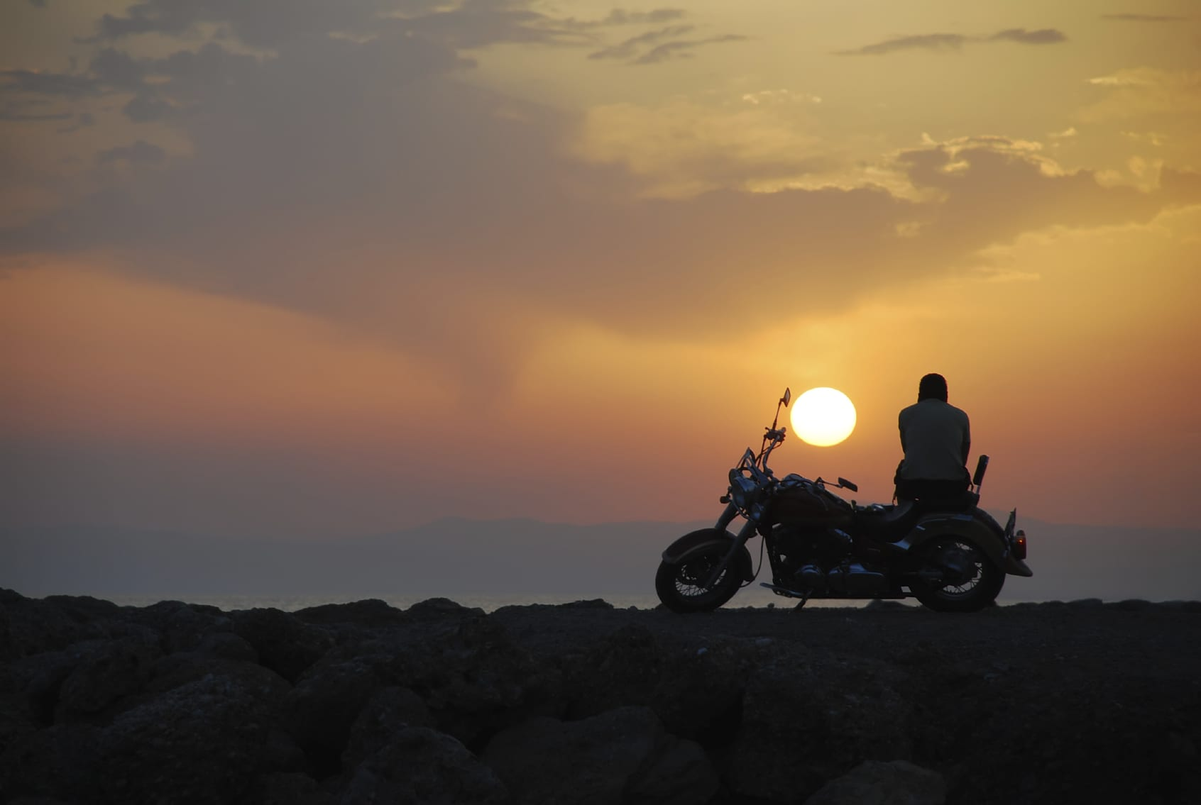 Motorcyclist Viewing Sunset While Sitting On Parked Motorcycle
