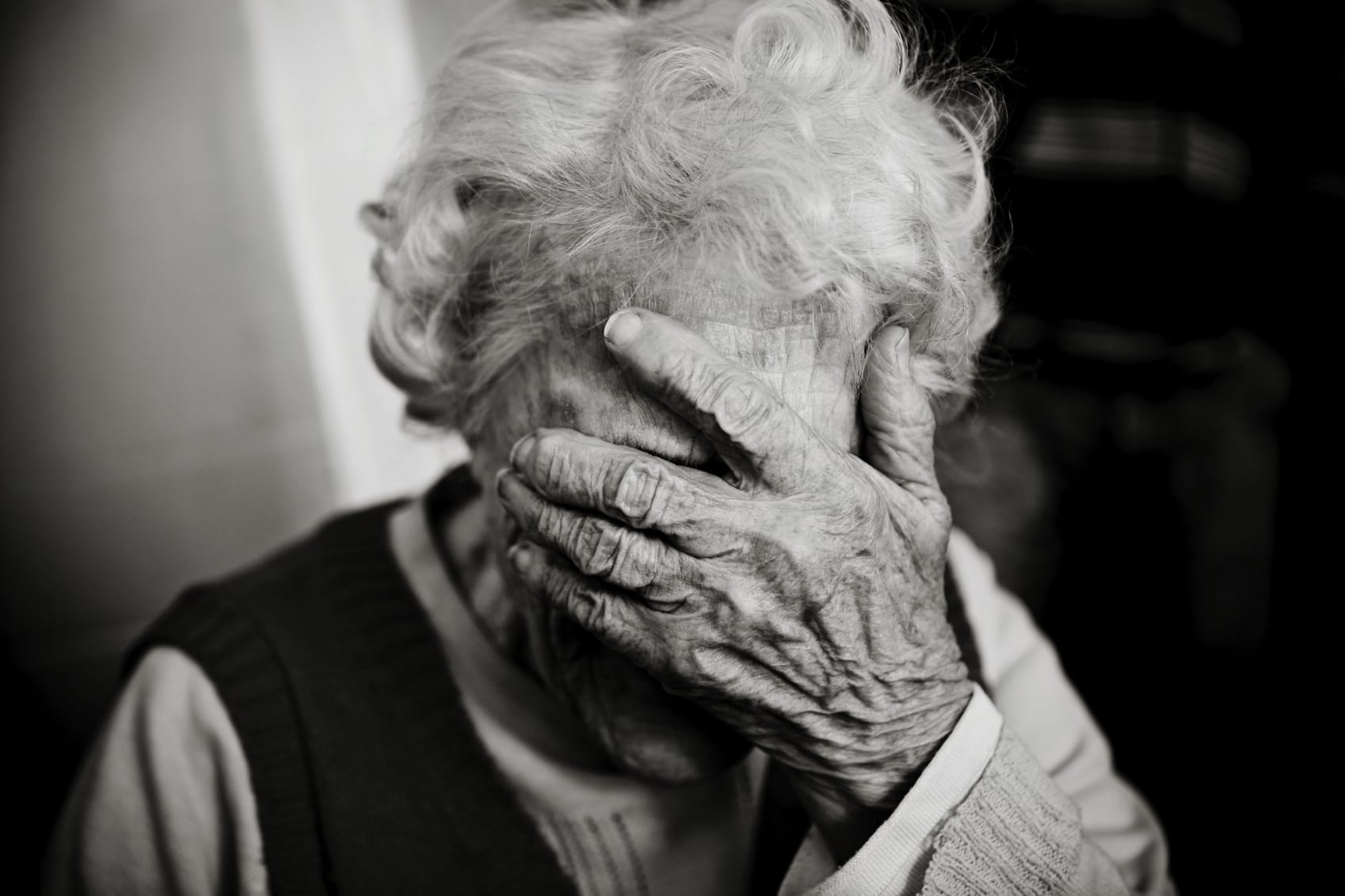 Elderly Woman With Her Hands Over Her Eyes Stock Photo