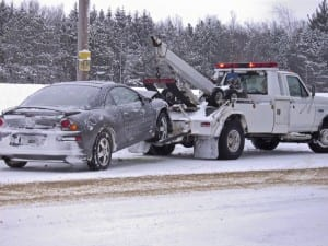 Tow Truck Towing Vehicle During Snowstorm Stock Photo