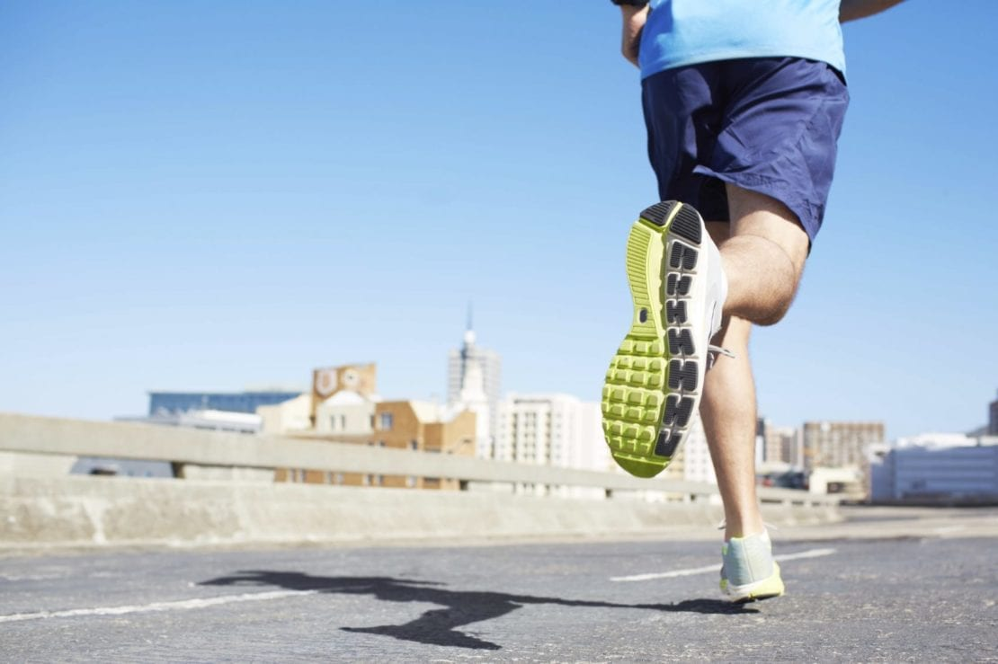 Young Man Running Downtown In A Large City Stock Photo