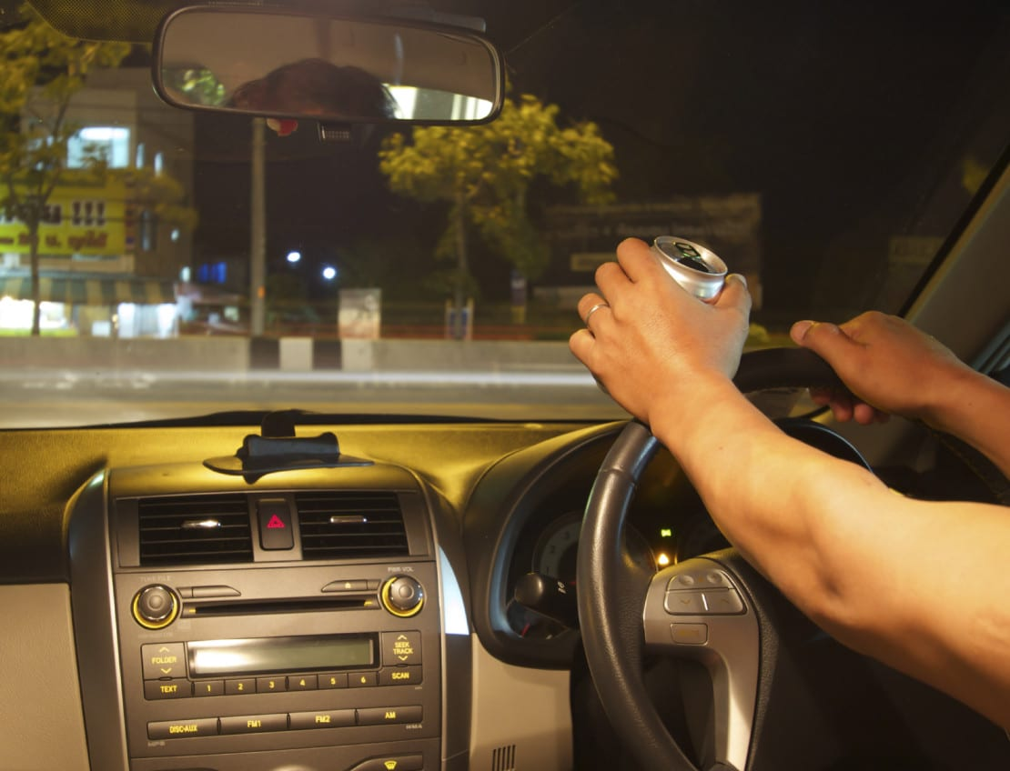 Man Drinking Alcohol While Driving At Night Stock Photo