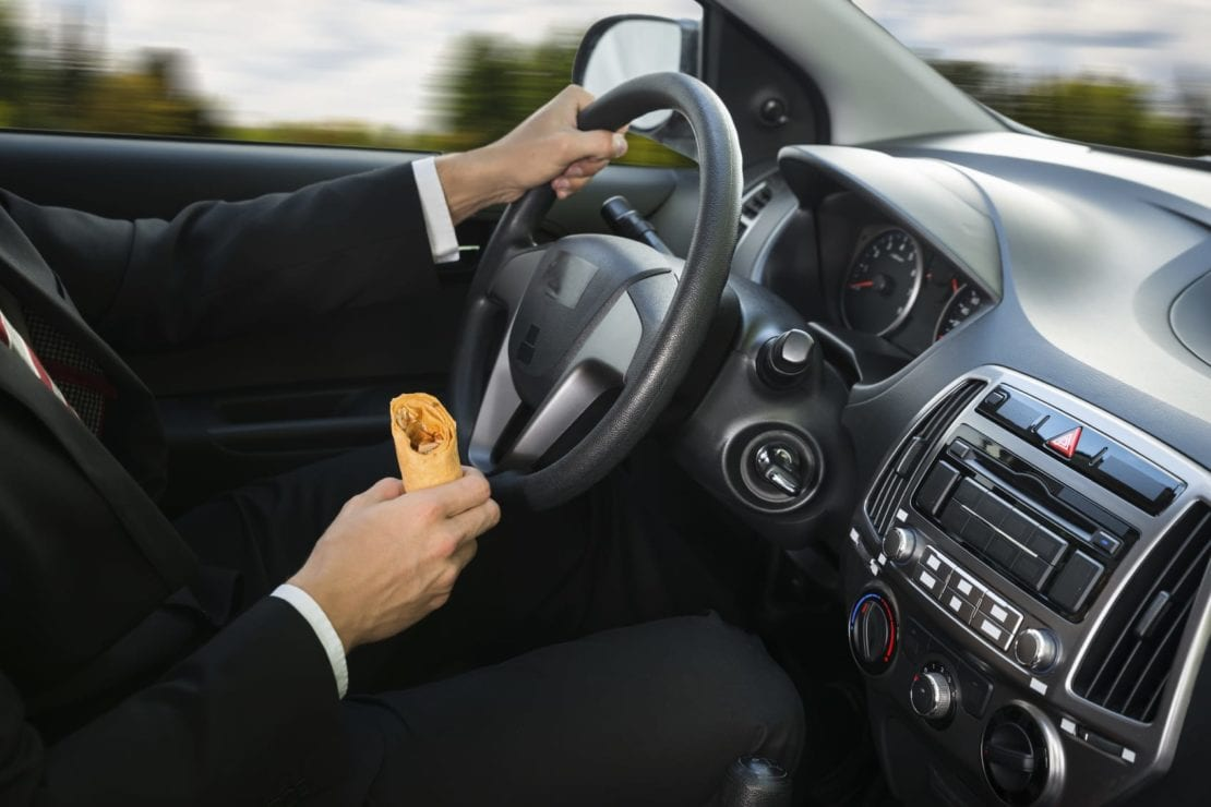 Man Eating While Driving Stock Photo