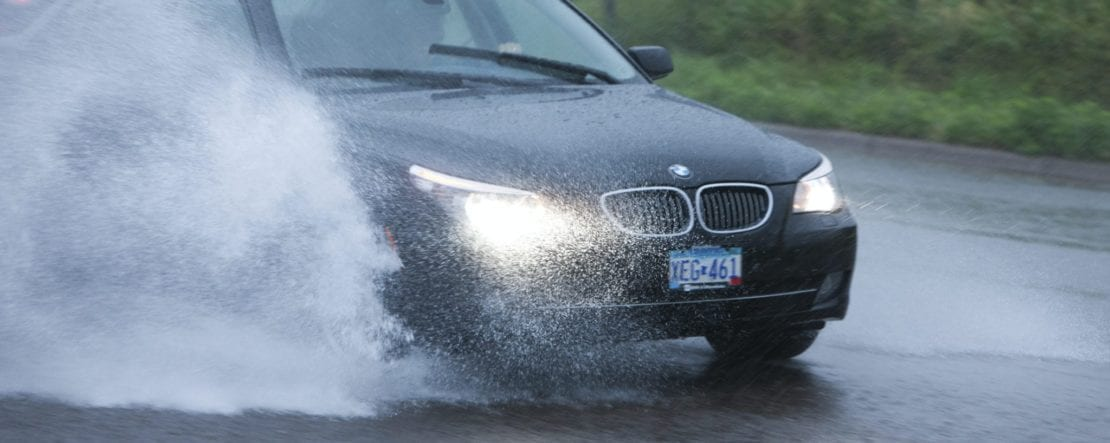 Black BMW Driving During Heavy Rainfall