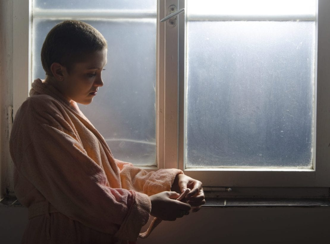 Young Cancer Patient Staring Out A Window Inside A Hospital