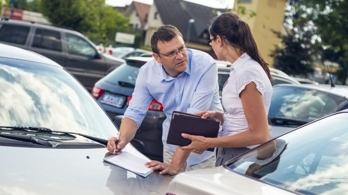 Man And Woman Exchanging Insurance Information After Car Accident Stock Photo