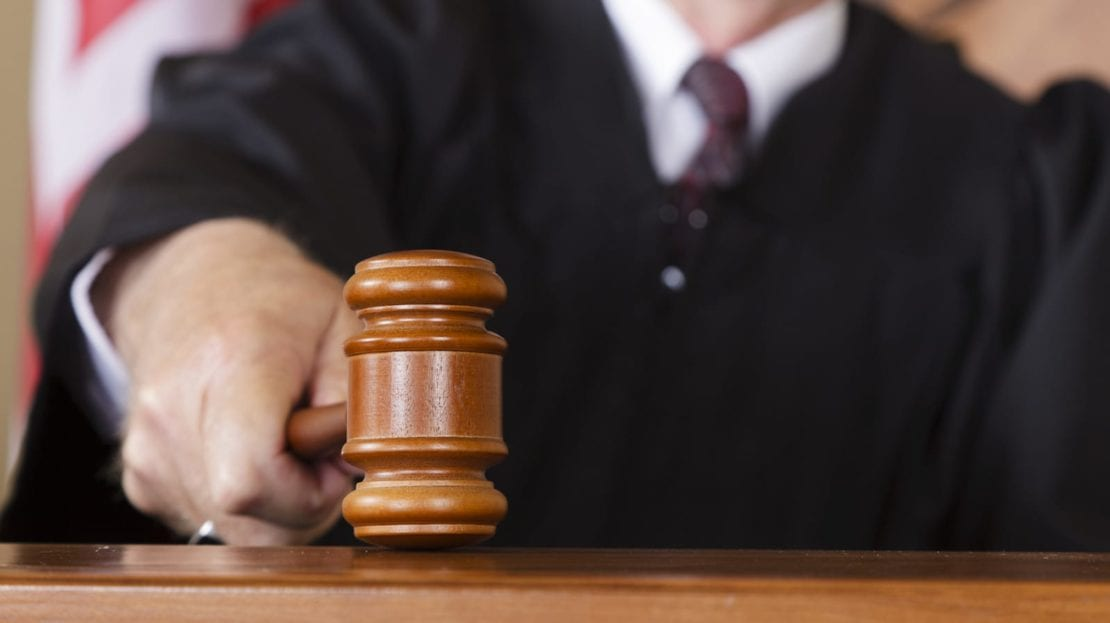 Judge Slamming Down Gavel Inside Courtroom Stock Photo
