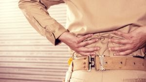 Blue Collar Worker Experiencing Lower Back Pain Stock Photo