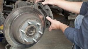 Mechanic Installing New Brakes On A Vehicle Stock Photo