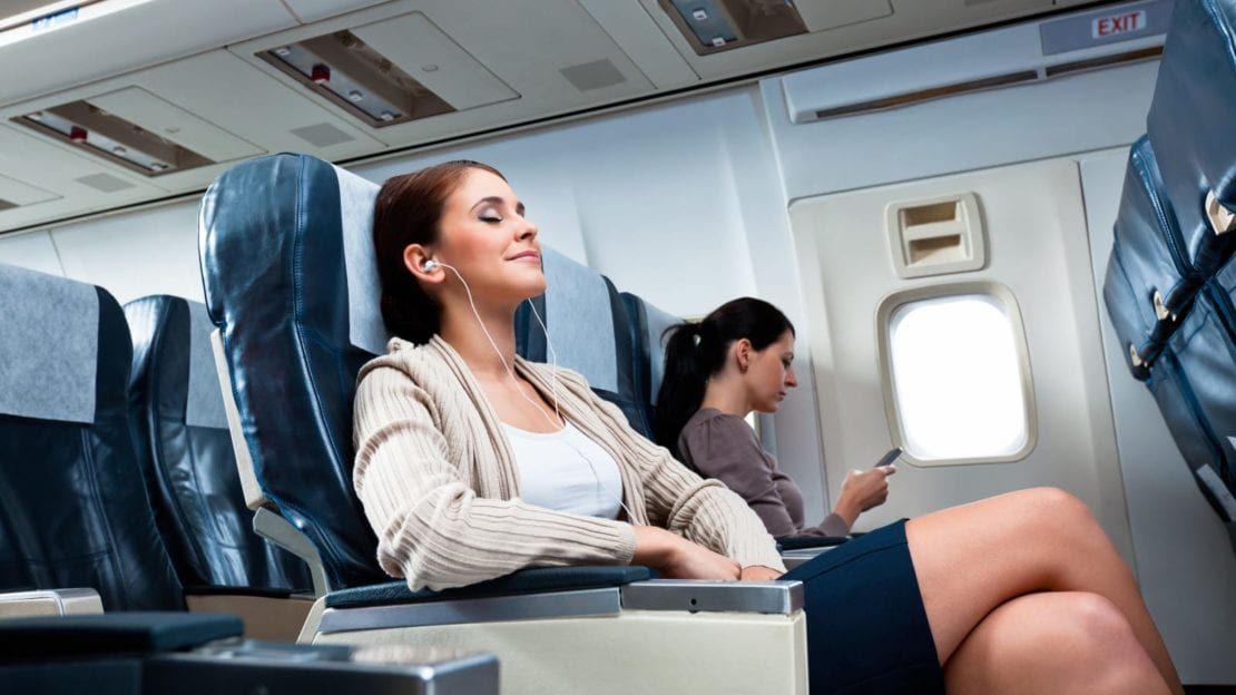 Young Woman Relaxing During A Long Flight Stock Photo