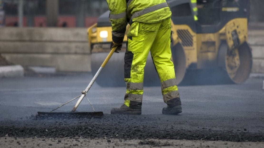 Road Construction Worker Laying Blacktop Stock Photo
