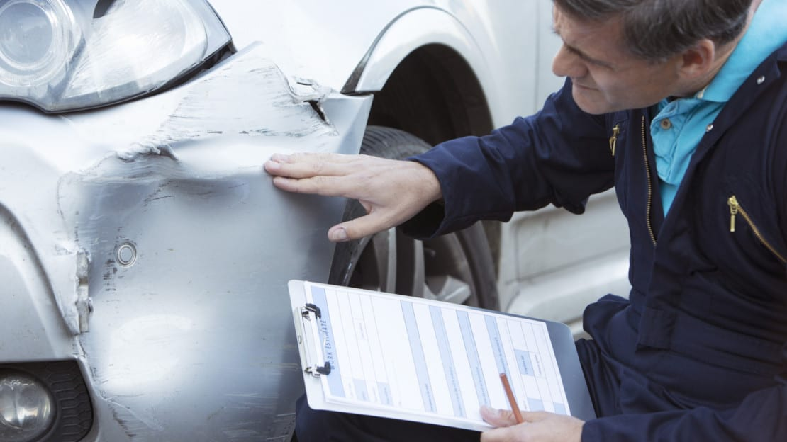 Auto Body Mechanic Examining Car Accident Damage Stock Photo
