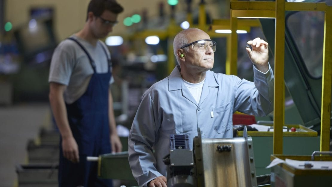 Blue Collar Worker Working Inside A Factory Stock Photo