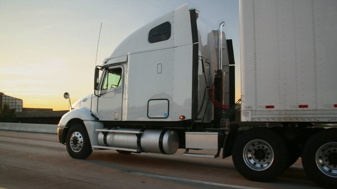 White Semi-truck Driving On The Interstate Stock Photo