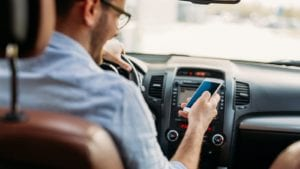 Young Man Texting While Driving His Vehicle Stock Photo