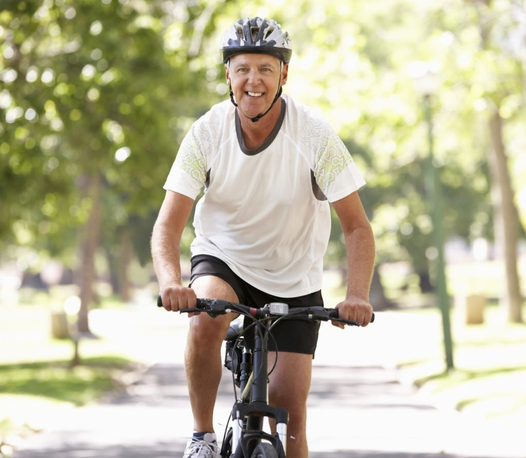 Mature Man Riding His Bicycle On A Bike Path Stock Photo