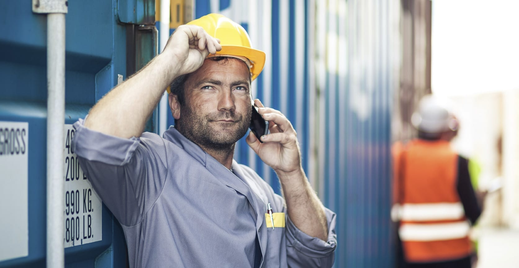 Construction Worker In Hard Hat Talking On Mobile Device Stock Photo