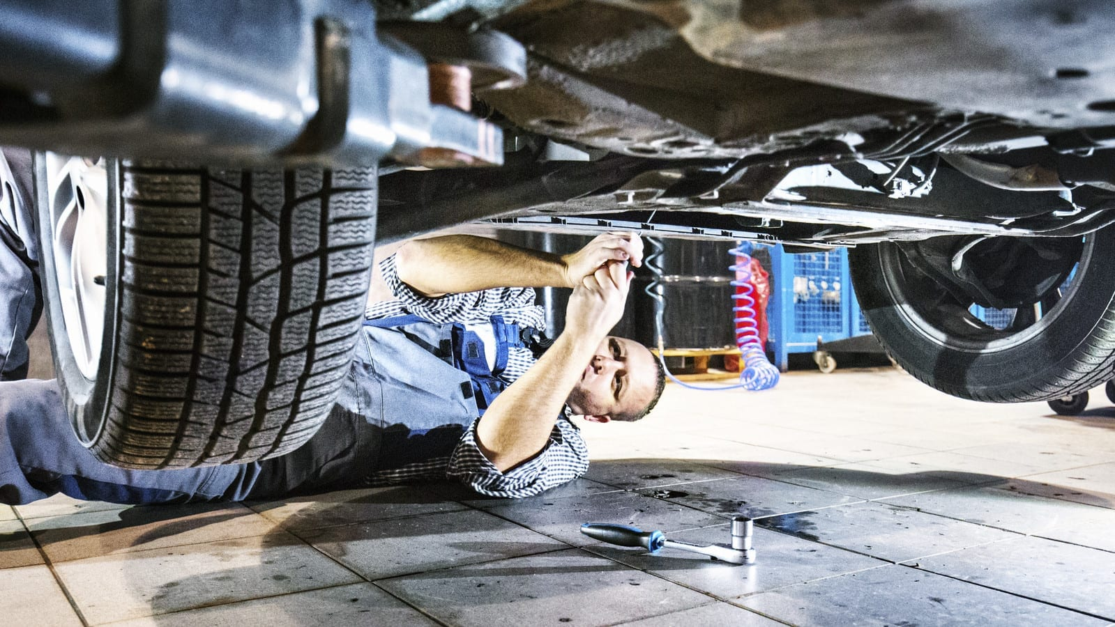 Mechanic Working Underneath A Vehicle Stock Photo