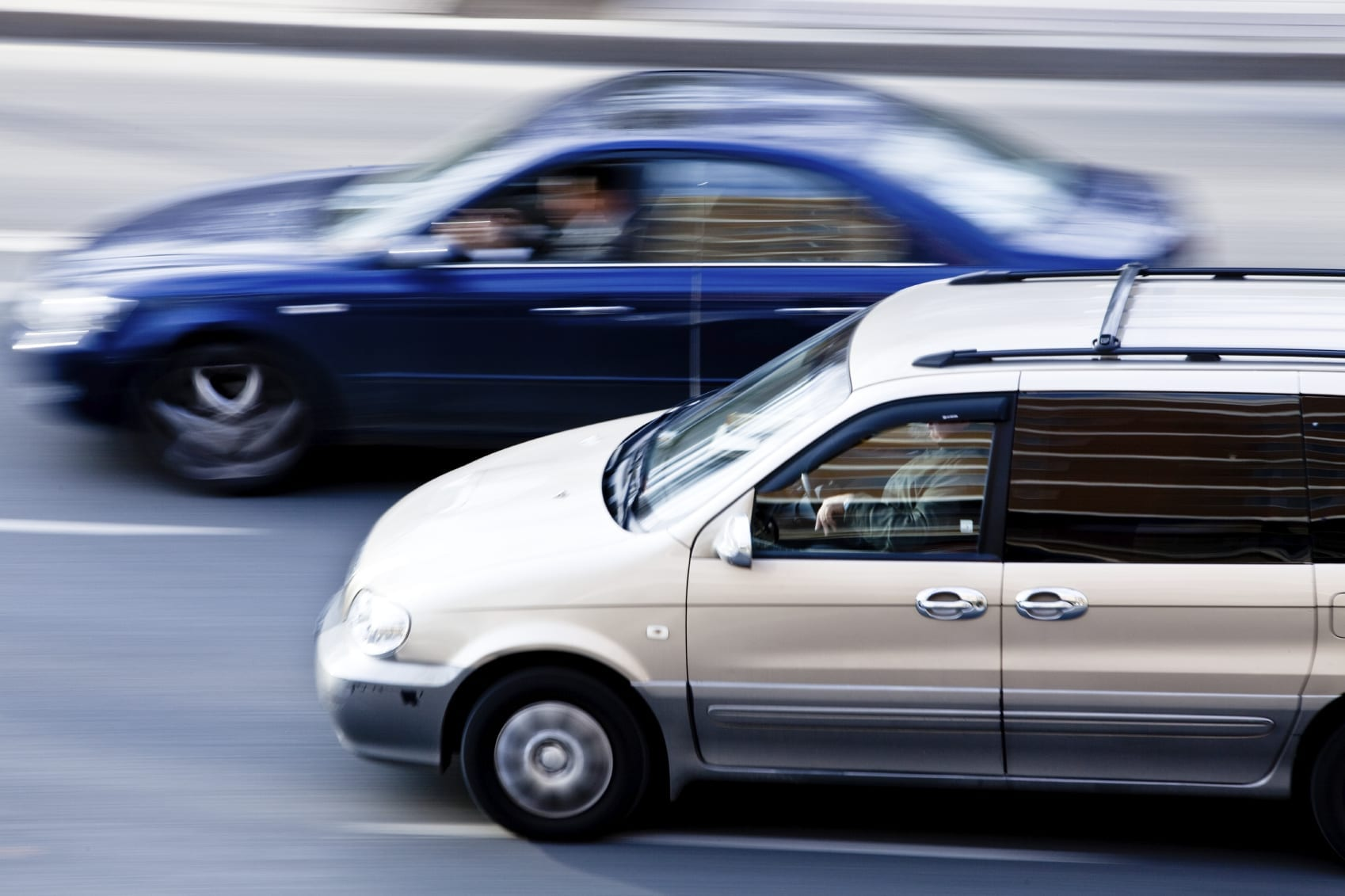 Minivan Passing A Blue Car On The Highway Stock Photo