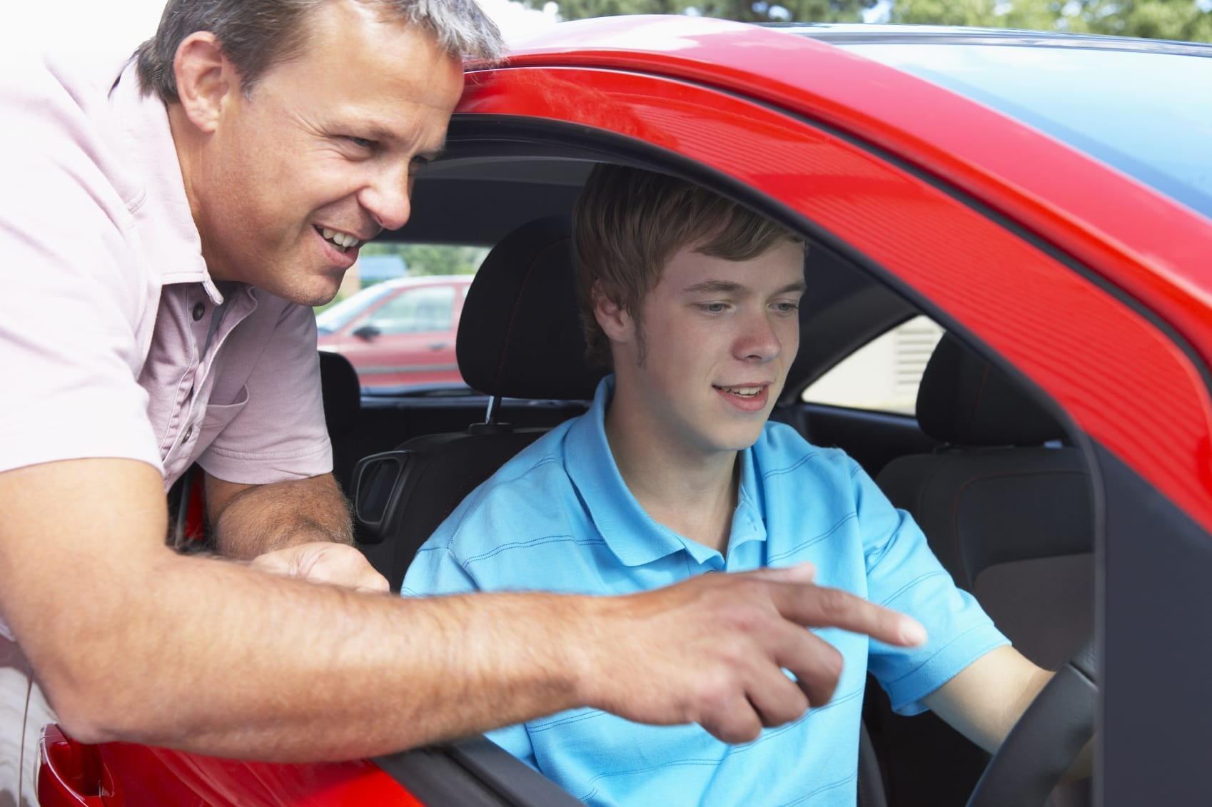 Father Giving Driving Tips To Teenage Son Stock Photo