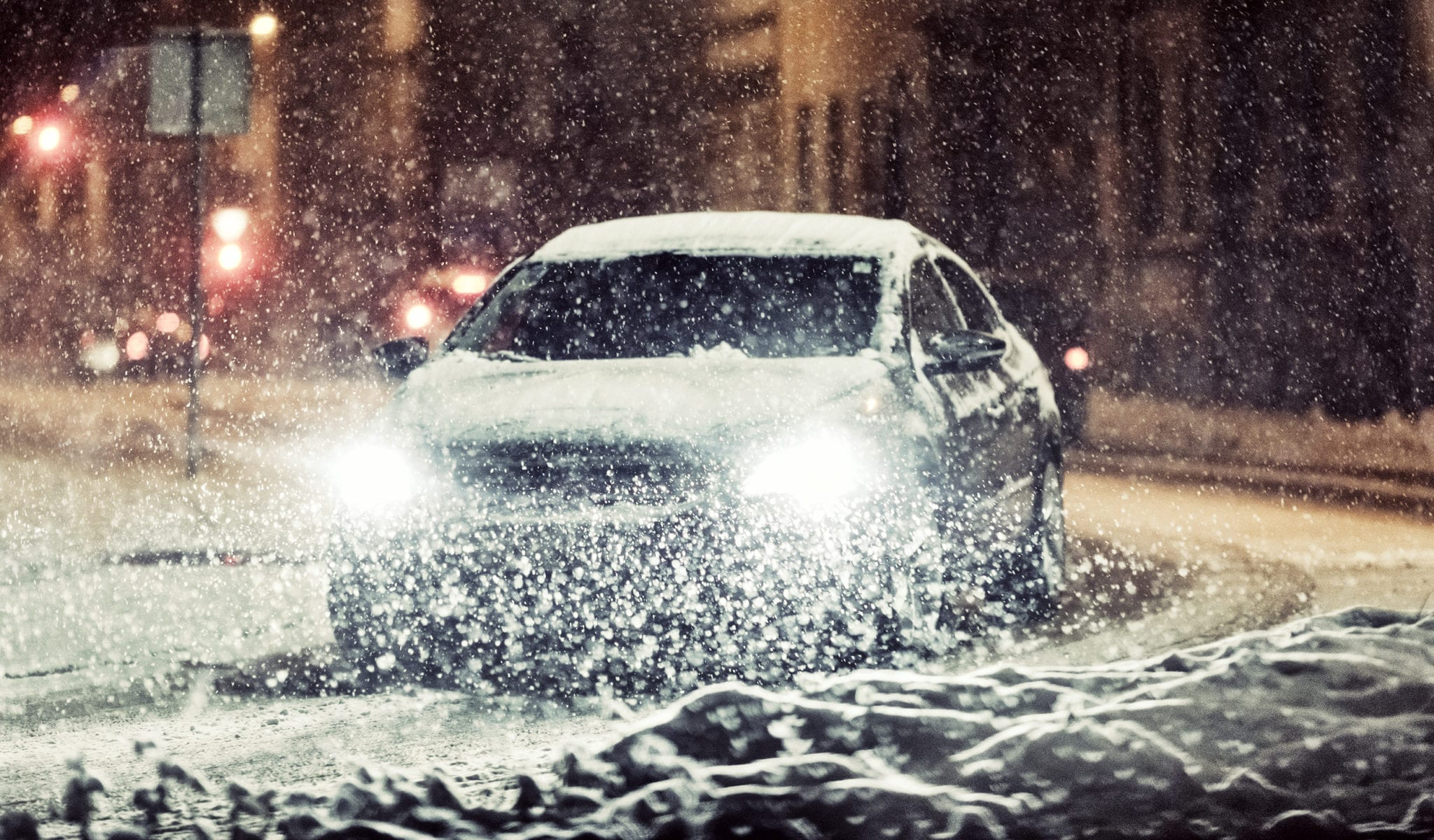 Car Driving In A City During Heavy Snowfall Stock Photo