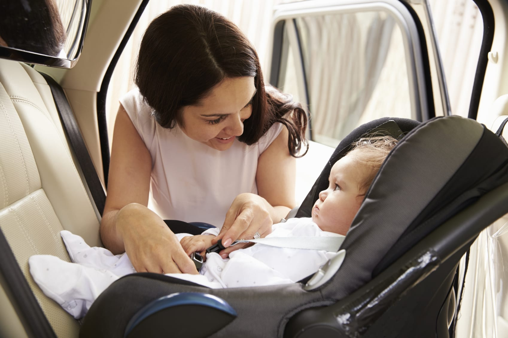 Young Woman Fastening Infant Baby Into Car Seat Stock Photo