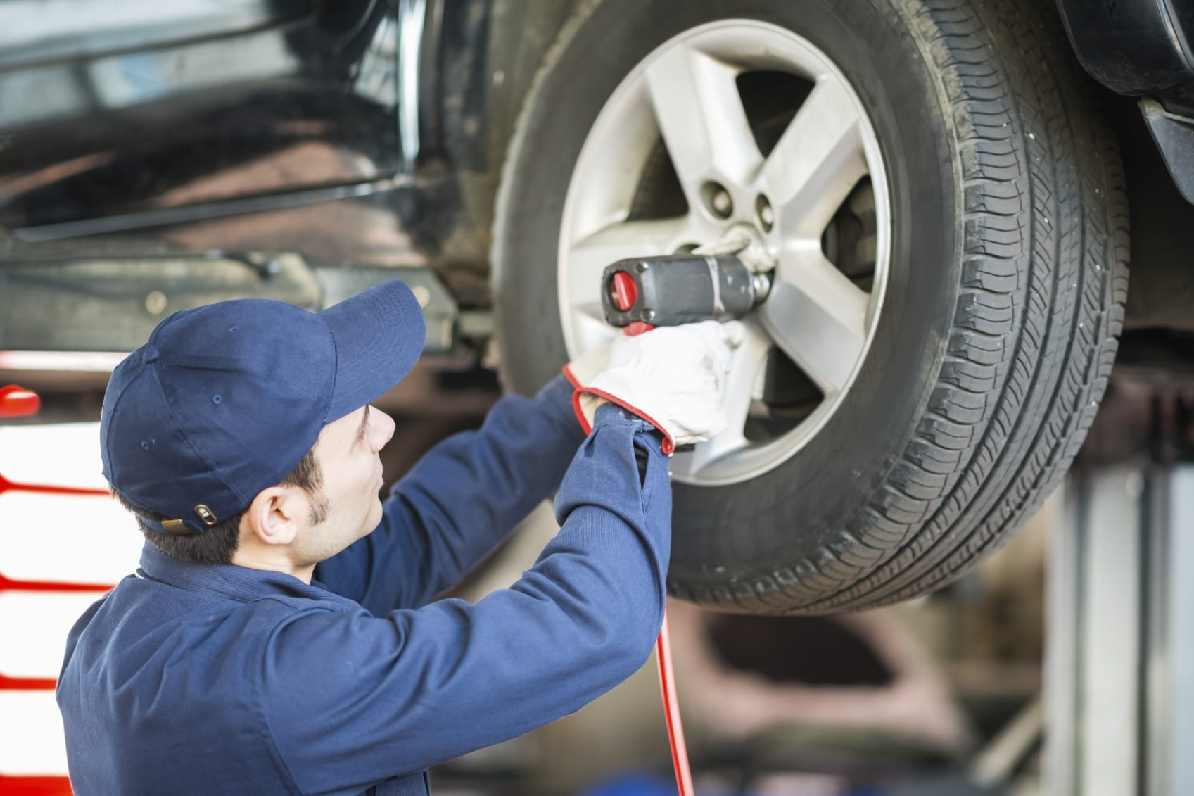 Mechanic Adding New Tire To Vehicle Stock Photo