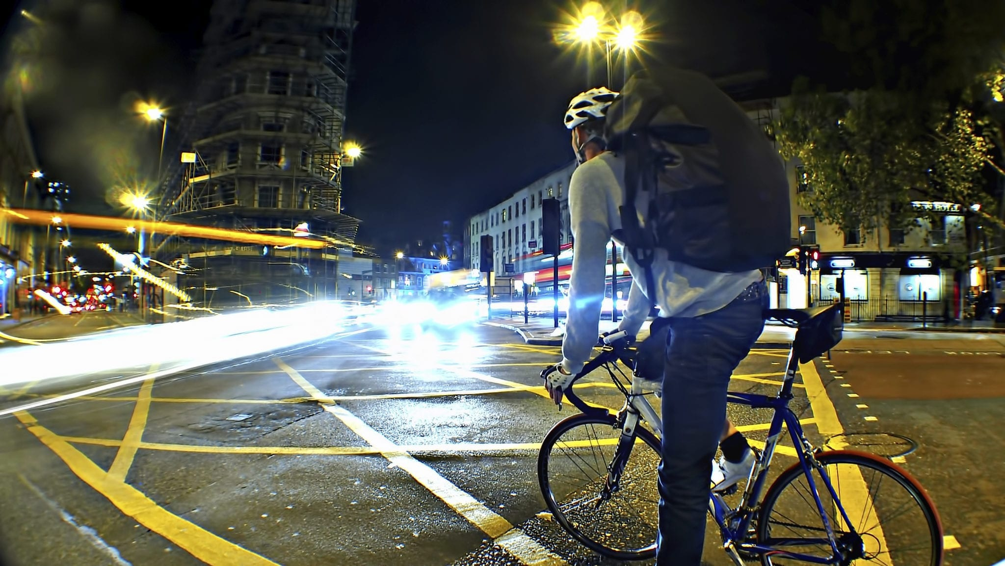 Man Riding Bicycle On City Street At Night Stock Photo