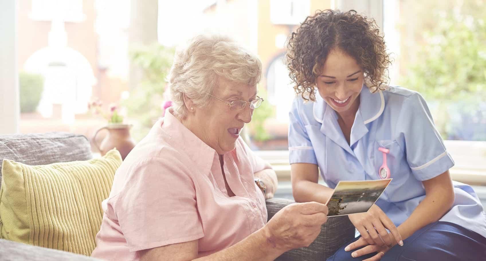 Nurse Spending Time With Elderly Resident At Nursing Home