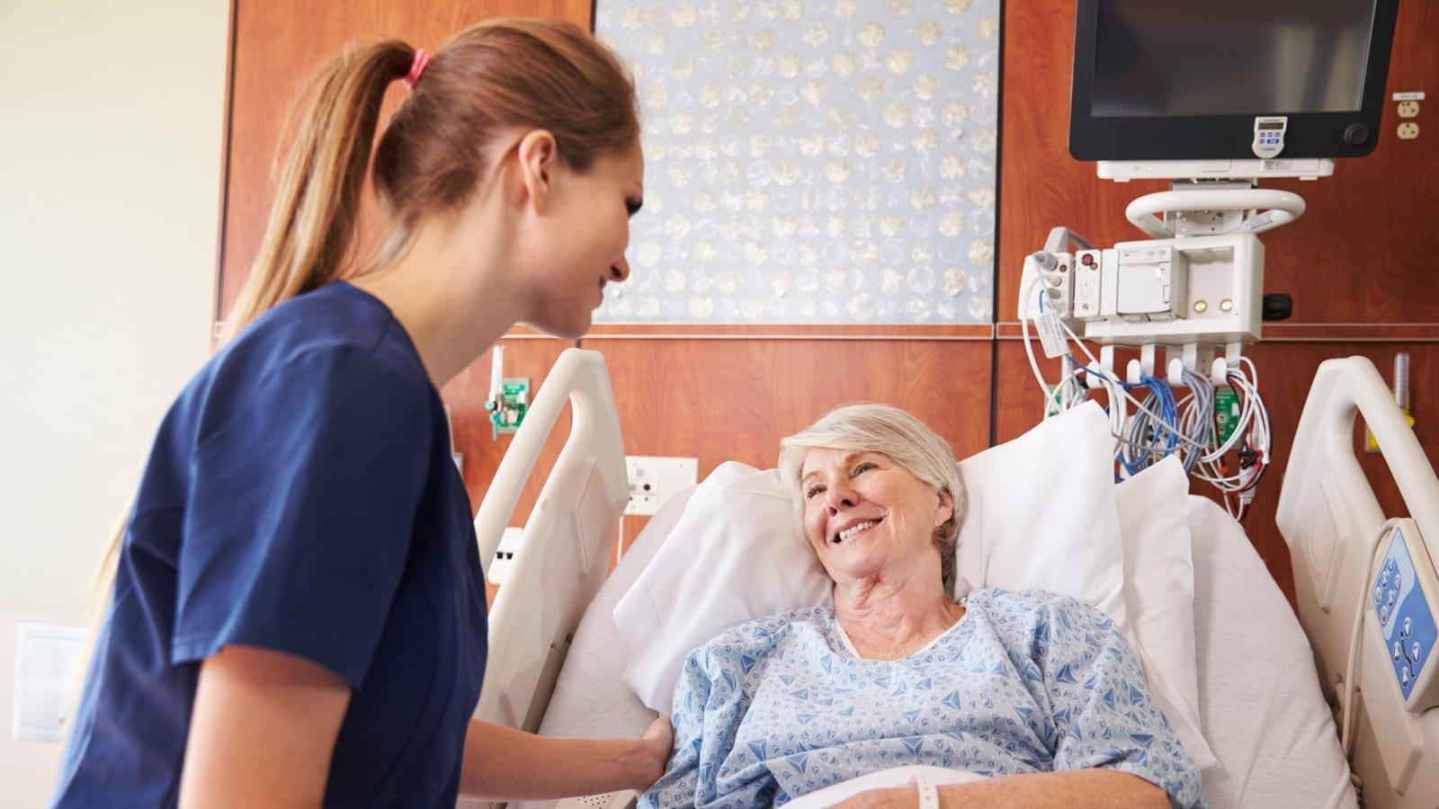 Female Nurse Consoling Elderly Female Patient Stock Photo