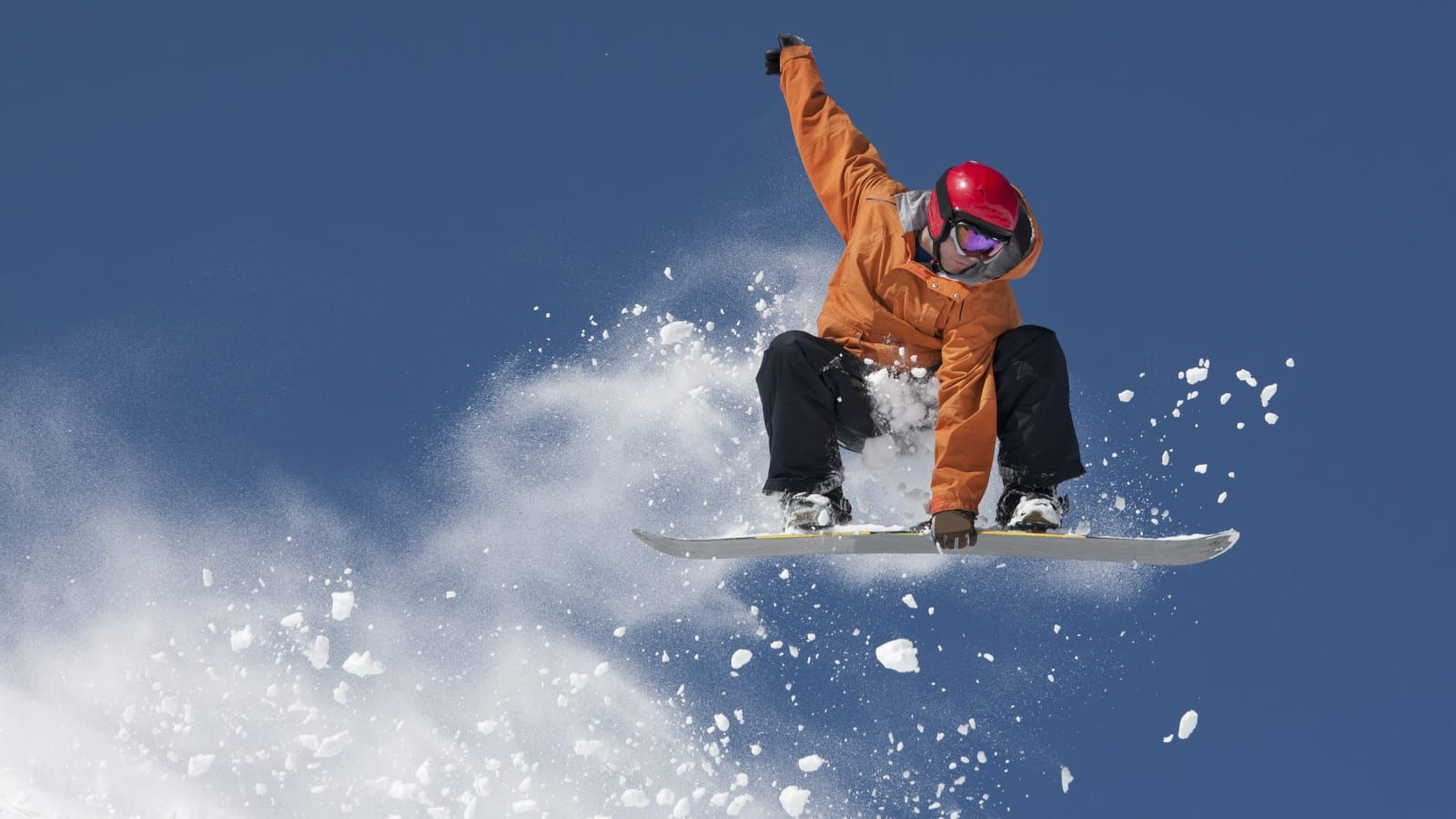 Young Man Flying Through The Air On A Snowboard Stock Photo