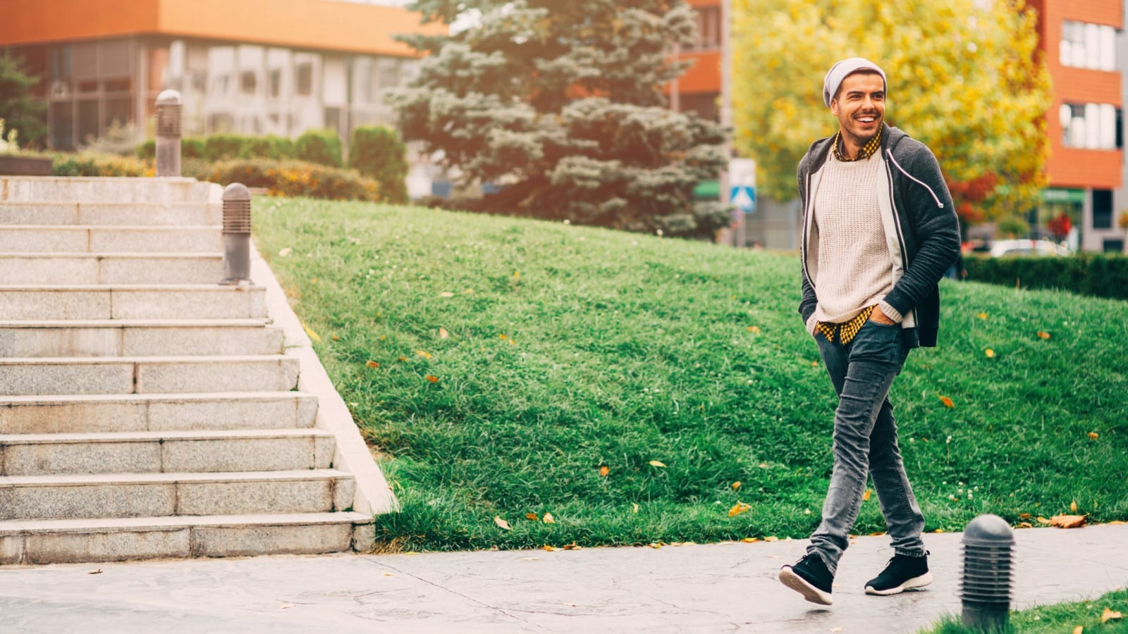 Young Man Walking Alone On A Sidewalk Stock Photo