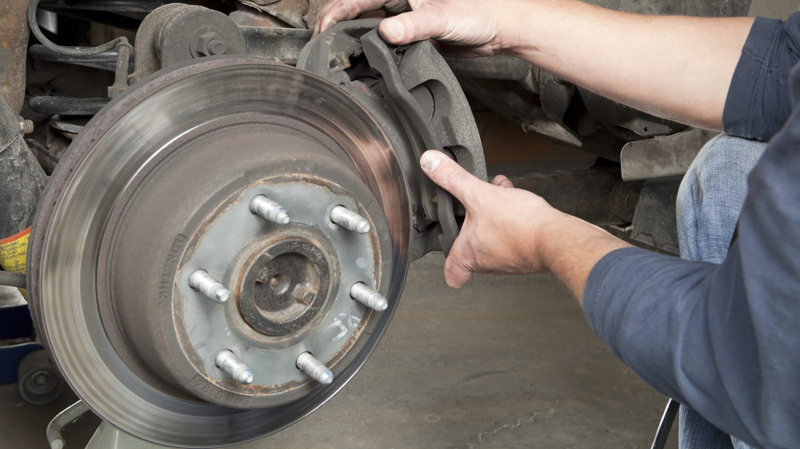 Mechanic Installing New Brakes On A Vehicle Stock Photo