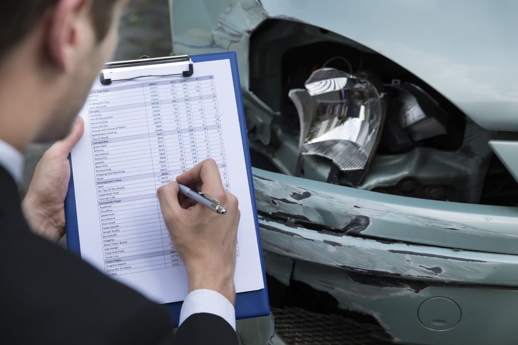 Insurance Agent Reviewing Damage To Vehicle Stock Photo