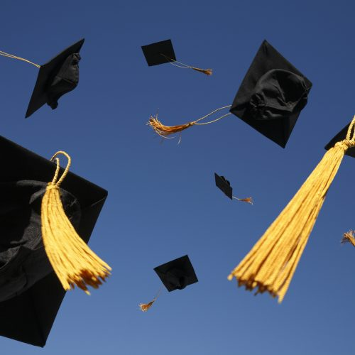 Graduation caps tossed in the air.